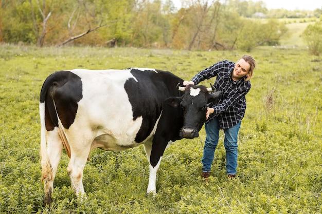 Donna con una mucca in fattoria