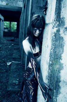 Donna con trucco creativo. zombie cyber femminile. edificio distrutto.