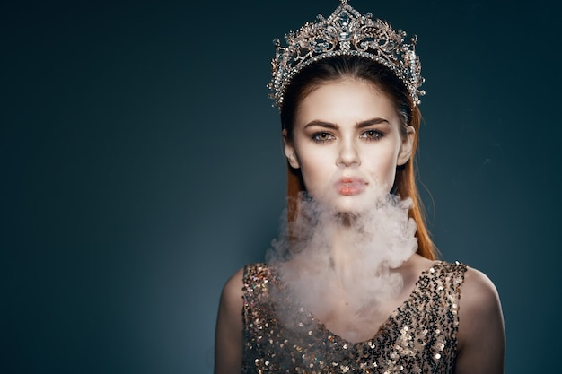 Donna con una corona in testa fuma dalla bocca glamour lusso sfondo scuro