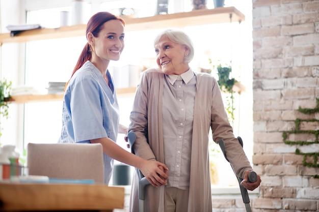 Donna con le stampelle che sorride mentre parlando con il badante