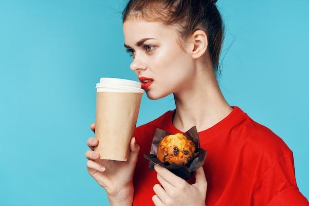 Donna con una tazza di caffè e un cupcake in mano cibo dietetico per la colazione