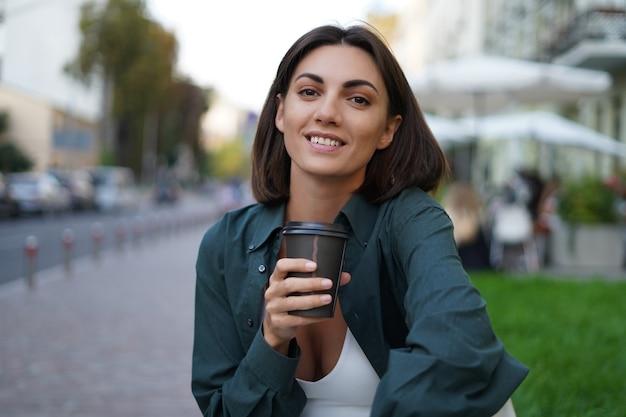 Donna con una tazza di caffè all'aperto in una strada di città al tramonto sorridenti godendosi le giornate estive
