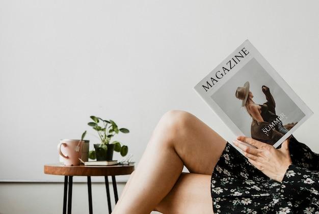 Donna con una tazza di tè che legge una rivista