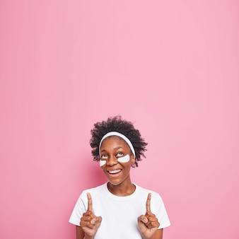 Donna con capelli ricci applica cerotti di bellezza sotto gli occhi indica sorrisi verso l'alto si sottopone delicatamente a trattamenti per la cura della pelle vestita con maglietta bianca isolata su rosa