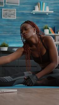 Donna con la pelle scura che fa allenamento di pilates in soggiorno allungando i muscoli del corpo