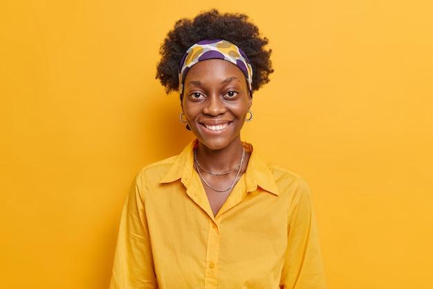 Donna con la pelle scura sorride positivamente felice di ricevere un complimento esprime emozioni allegre arriva su una riunione informale indossa una camicia casual isolata sul muro giallo