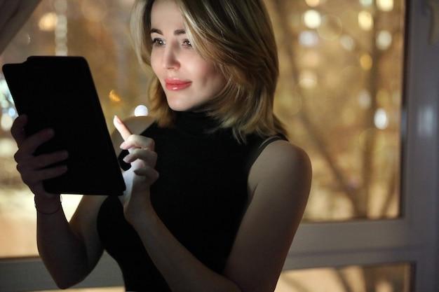 Donna con tavoletta digitale vicino alla finestra di notte