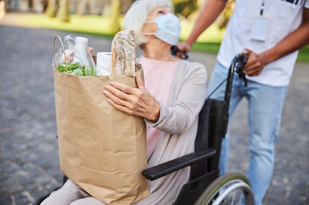 Donna con disabilità seduta su una sedia a rotelle e si gira verso una persona in piedi dietro la sua borsa mentre tiene in mano un sacchetto di carta con gli acquisti