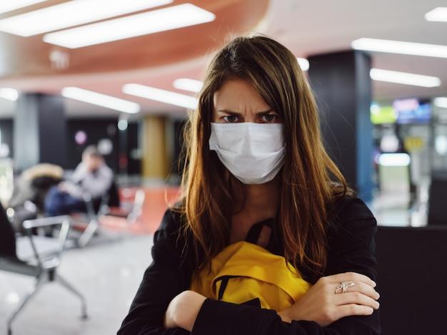 Una donna con un'espressione facciale scontenta che indossa una maschera medica si siede all'aeroporto