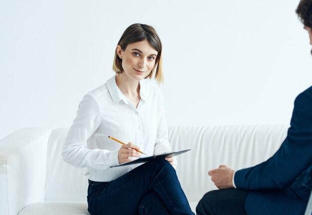 Una donna con documenti ascolta i problemi di un uomo su uno psicologo di sfondo chiaro