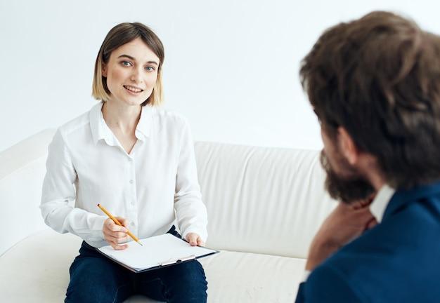 Donna con documenti e un uomo in giacca e cravatta seduto sul divano che assume posti di lavoro