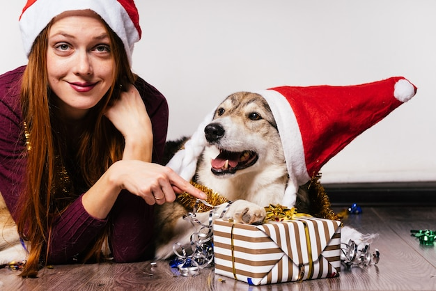 La donna con un cane con un cappello di natale giace su uno sfondo di regali