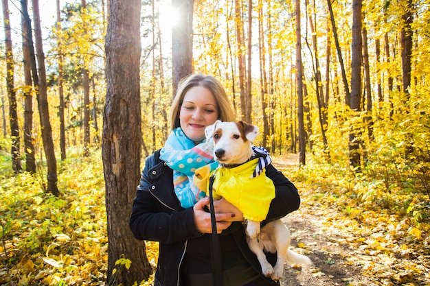 Donna con un cane jack russell terrier nel parco autunnale