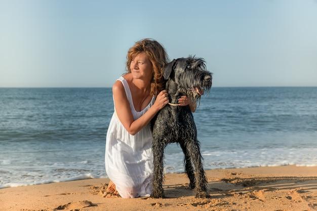 Donna con cane in riva al mare guardando il paesaggio