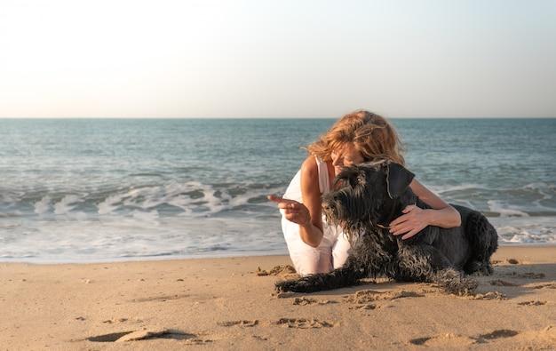 Donna con cane sul puntamento in riva al mare