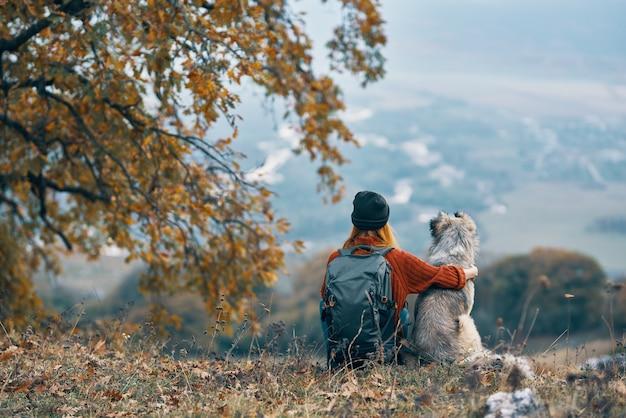 La donna con il cane si siede per terra nelle montagne della natura