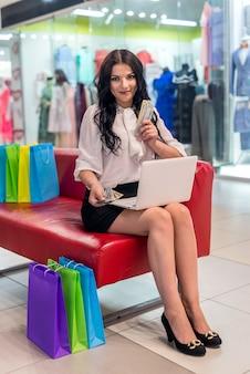 Donna con ventilatore dollaro e computer portatile seduti nel centro commerciale