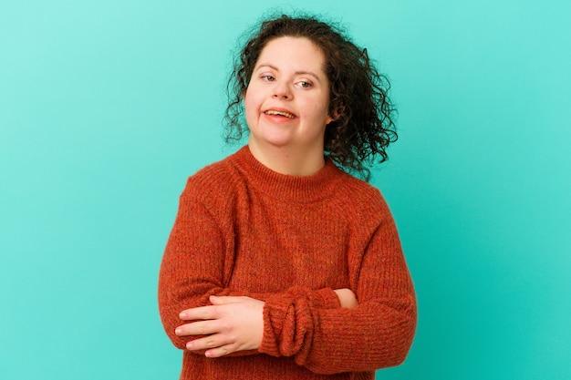 La donna con la sindrome di down aggrotta la fronte per il dispiacere, tiene le braccia conserte.