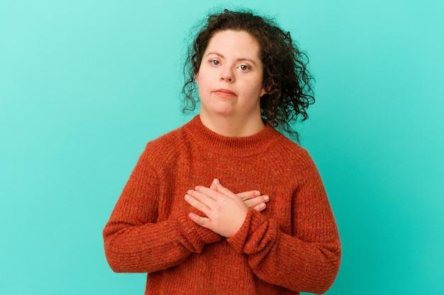 La donna con sindrome di down isolata ha un'espressione amichevole, premendo il palmo contro il petto. concetto di amore.