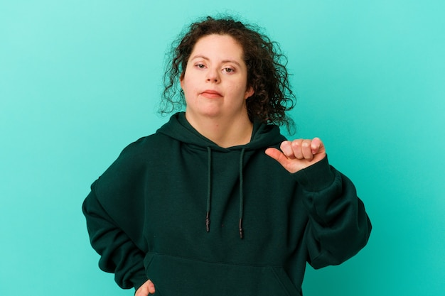Donna con sindrome di down isolata che mostra un gesto di antipatia, pollice in giù. concetto di disaccordo.