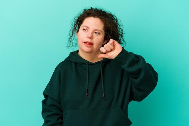 Donna con sindrome di down isolata che mostra il pollice verso il basso ed esprime antipatia.