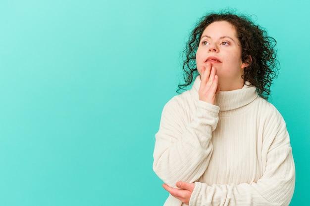 Donna con sindrome di down che guarda lateralmente con espressione dubbiosa e scettica.