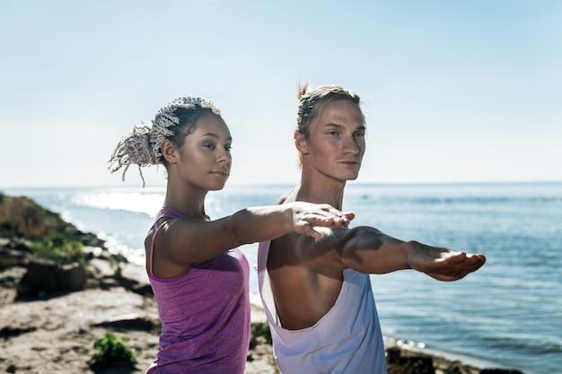 Donna con i dreadlocks. donna afro-americana con i dreadlocks che fa yoga con il suo bell'uomo in una giornata calda