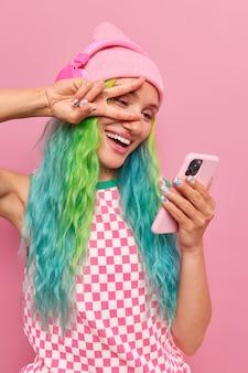 Donna con i capelli tinti fa un gesto di pace sull'occhio prende selfie ascolta musica in cuffie wireless fa videochiamata indossa un abito elegante utilizza moderne tecnologie per l'intrattenimento.