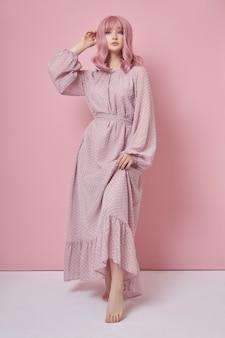 Donna con capelli rosa tinti in un vestito lungo. ritratto di una ragazza con la colorazione dei capelli al muro rosa. acconciatura e acconciature perfette