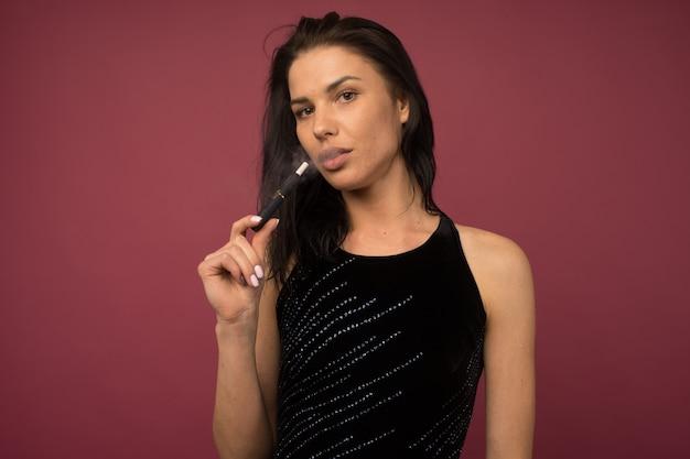 Donna con sigaretta elettronica. sistema di riscaldamento del tabacco le tecnologie di prodotto iqos
