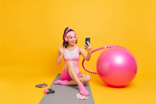Donna con aspetto orientale onde ciao nella fotocamera dello smartphone ha una videochiamata utilizza cuffie wireless si siede su karemat isolato su giallo