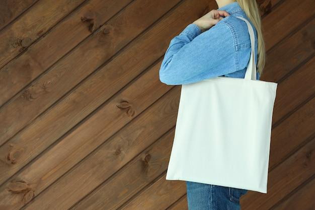 Donna con borsa eco contro la superficie in legno