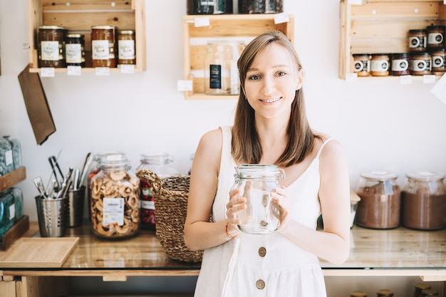 Donna con barattolo di vetro vuoto che acquista in un negozio di alimentari senza plastica sostenibile negozio di rifiuti zero