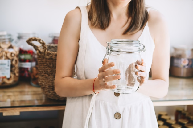 Donna con barattolo di vetro vuoto che acquista in un negozio di alimentari senza plastica sostenibile negozio di rifiuti zero Foto Premium