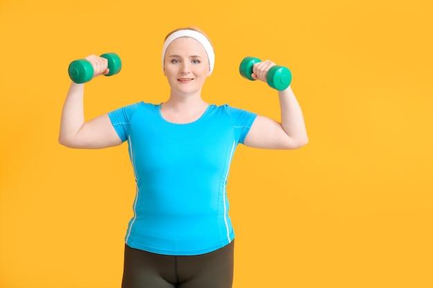 Donna con allenamento con i pesi in eccesso sul colore