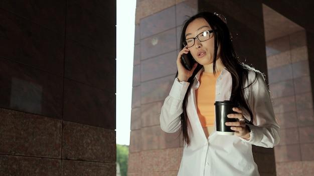 La donna con gli occhiali si avvicina all'edificio degli uffici e parla al telefono la giovane ragazza asiatica si prende una pausa mentre lavora con il caffè per strada