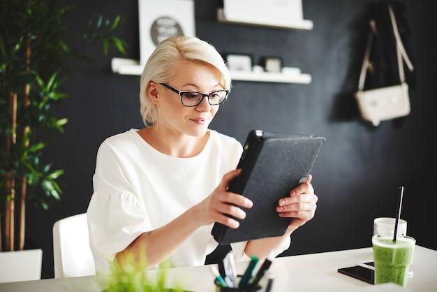 Donna con gli occhiali che utilizza una tavoletta digitale