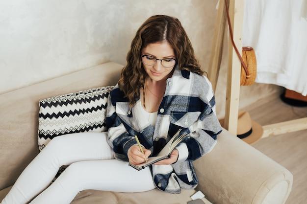 Donna con gli occhiali che scrive appunti con la penna in un blocco note seduta sul divano