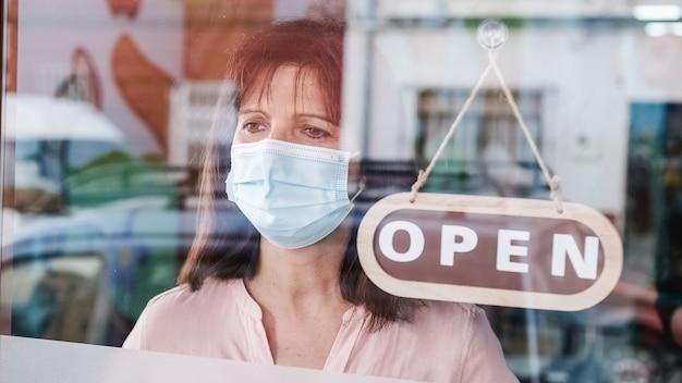 Donna con maschera facciale cambiando chiuso per aprire il segno sulla finestra che guarda fuori