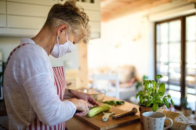 Donna con maschera facciale che cucina al chiuso a casa, quarantena e concetto di virus corona.