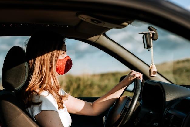 Donna con maschera facciale alla guida di un'auto