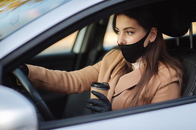 Donna con maschera facciale alla guida della sua auto con una tazza di caffè durante la pandemia di coronavirus,