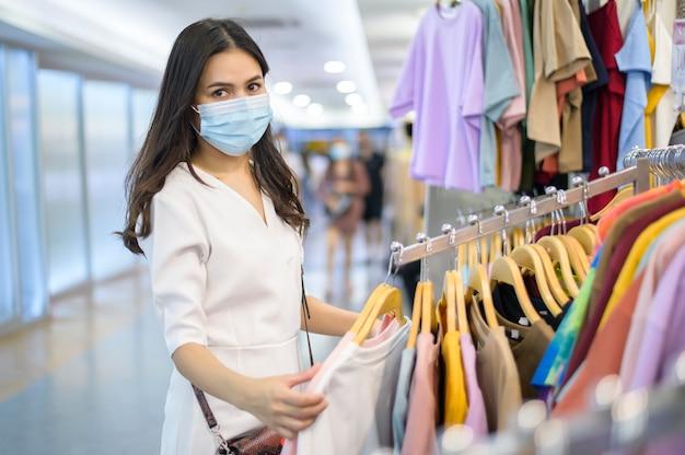 Donna con la maschera per il viso è lo shopping di vestiti nel centro commerciale