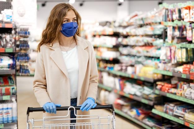 Donna con maschera facciale che utilizza il carrello della spesa al supermercato durante la pandemia di coronavirus.