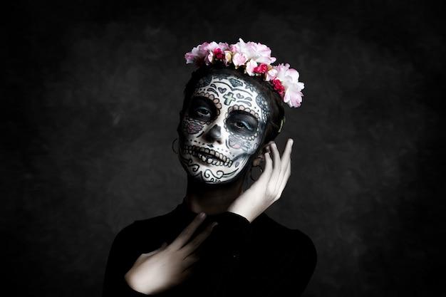 Donna con il viso dipinto come una catrina e fiori tra i capelli su sfondo scuro. giorno della morte