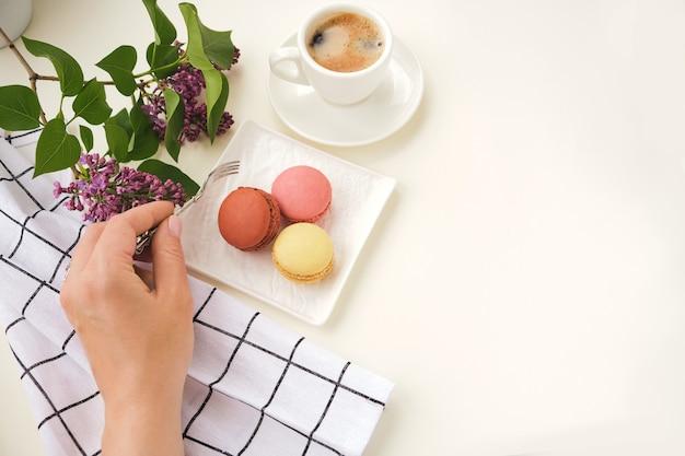 Donna con forchetta, tazza di caffè, macaron torta sul tavolo luminoso dall'alto