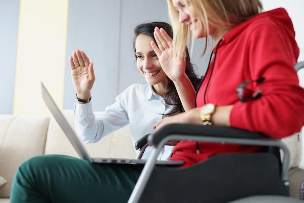 Donna con un amico seduto in sedia a rotelle e tenendo il portatile agitando per monitorare