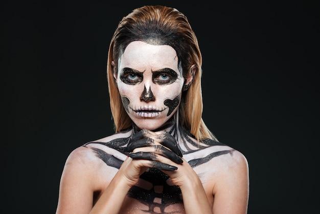 Donna con trucco scheletro spaventoso su sfondo nero