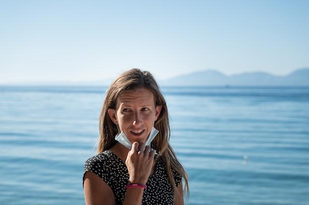 Donna con un cipiglio sul viso in piedi in riva al mare togliendosi la maschera protettiva medica.