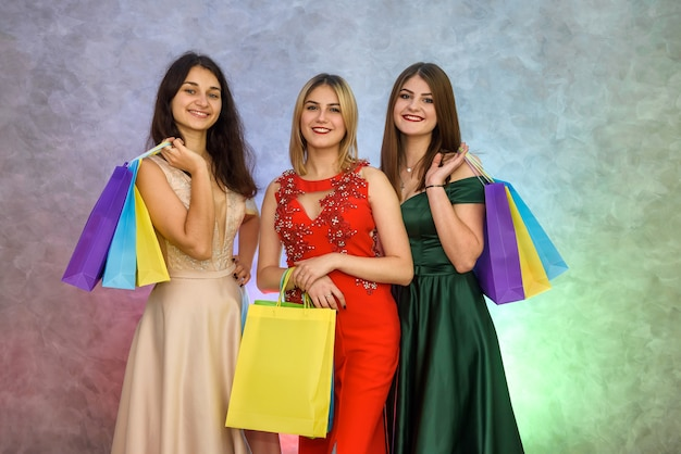 Donna con sacchetti regalo alla festa di capodanno in posa in eleganti abiti da sera
